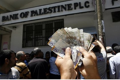 PA employees withdraw cash from Gaza bank after wthey were reopened