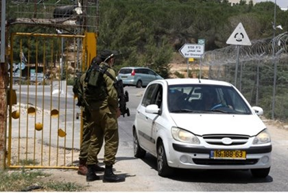 Israeli soldiers stand guard at the entrance to Kibbutz Kfar Etzion