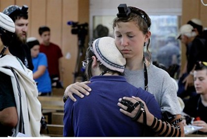 Classmates of kidnapped boys comfort each other after prayer service at Makor Chaim High School