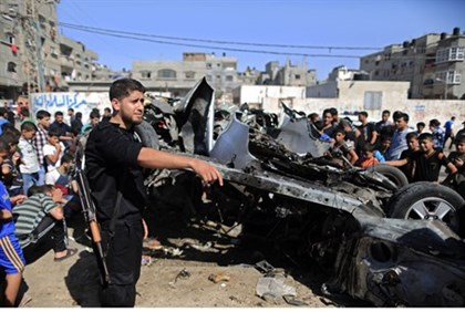Palestinians gather round wreckage of car targeted by IAF in Gaza's Shati refugee camp