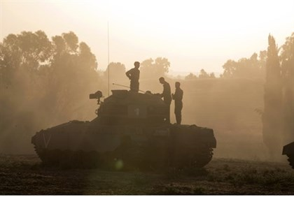 IDF soldiers stand atop an armored personnel carrier near the Gaza border