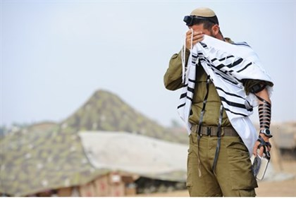 IDF soldier prays near the front line, close to Gaza