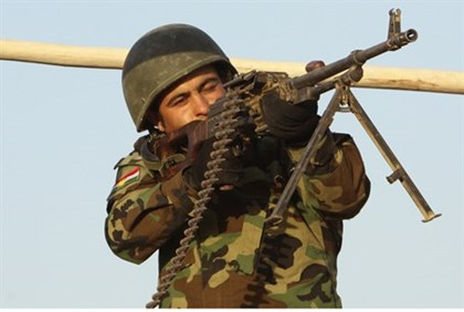 A member of Kurdish Peshmerga forces takes aim on frontline with Islamic State