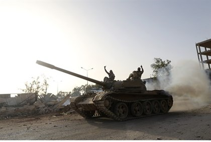 Benghazi Shura Council fighters gesture from a tank