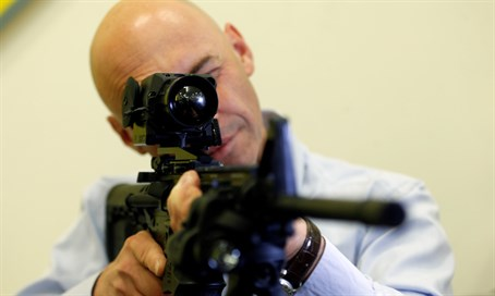 Man looks through infrared scope on a weapon during a preview presentation at Elbit Systems demo