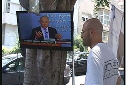 Tent protesters watch Netanyahu