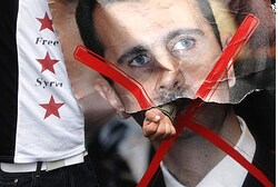 A demonstrator punches through a portrait of President Assad 