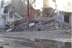 Debris and damaged houses after attack on Homs