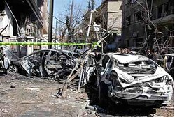 Damaged vehicles at the site after two explosions in Damascus