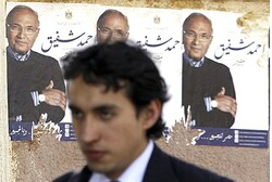 Man walks past campaign posters for Ahmed Shafiq