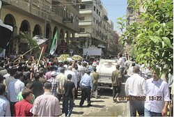 Anti-government protesters walk near coffins in Douma