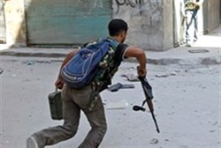 Free Syrian Army fighter runs across a street dodging Syrian Army bullets in the Salah al- Din neig