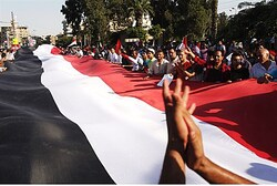 Anti-Morsi protesters hold a large Egyptian flag and chant slogans
