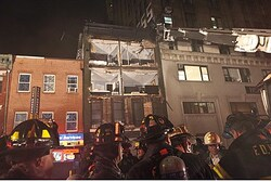 Fire fighters gather in front of a partially collapsed building in Manhattan