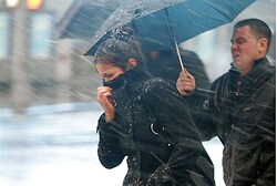 People walk through the wind and snow at New York's Times Square,