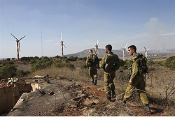 Israeli soldiers walk near Alonei Habashan close to the Israeli-Syrian border in the Golan Heights