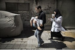 A Syrian man carries his wounded daughter in Aleppo