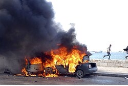 Anti-Morsi protesters run in front of burning cars in Alexandria