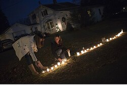 Residents light candles in their front yard for each victim of the Sandy Hook Elementary School