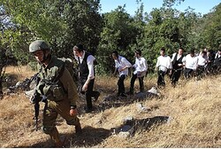An Israeli soldier escorts ultra-Orthodox Jews