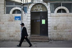 Jew walks next to synagogue