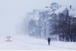 A pedestrian and a car make their way through a severe winter storm in Somerville, Massachusetts