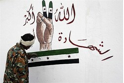A member of the Free Syrian Army paints on the Al-Moshat school wall in Aleppo