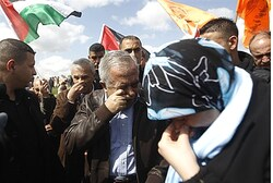 Palestinian Authority Prime Minister Salam Fayyad reacts from tear gas
