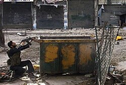A Syrian rebel aims his weapon during clashes with regime forces