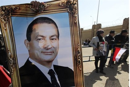Mubarak supporters hold up his photo