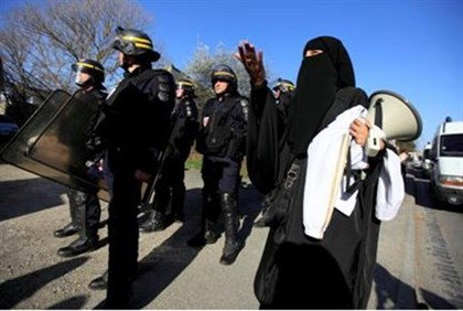 Veiled Muslim protests police raid on terrorist