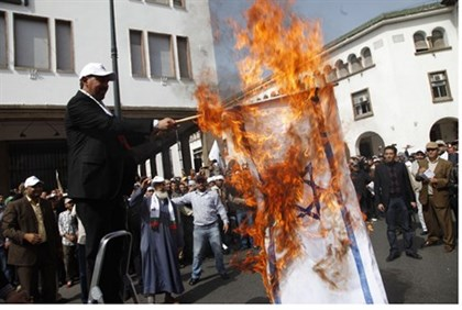 Protester in Rabat burns Israeli flag