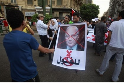 Protesters hold a poster of Shafiq
