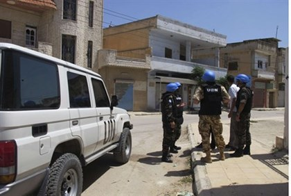 United Nations observers inspect a residential area in Syria