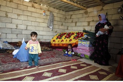 Syrian refugees sit in a temporary home in Lebanon