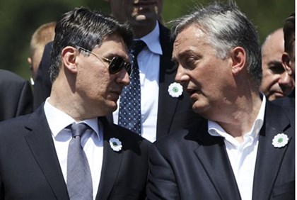 Croatian Prime Minister Zoran Milanovic (L) speaks to Bosnian Foreign Affairs Minister Zlatko Lagumd