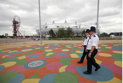 Police officers walk past the Olympic Stadium, in the Olympic Park, in Stratford, east London,