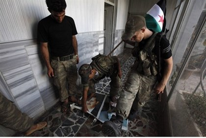 Free Syrian Army soldiers step on portraits of Assad
