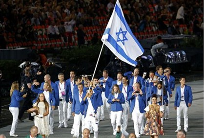 Israel's flag bearer Shahar Zubari holds the national flag as he leads the contingent in the athlete