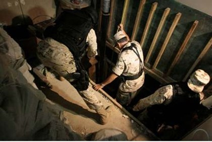 Mexican Soldiers inspect the entrance of a cross border tunnel running to California and seized some