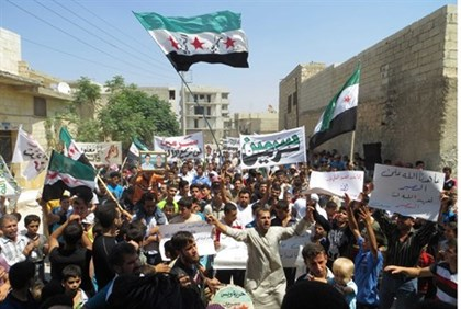 Demonstrators hold Syrian opposition flags during a protest against Assad