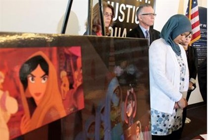 """Former Disney employee Boudlal next to poster with images of Princess Jasmine from ""Aladdin"