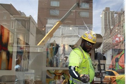Construction workers clean up an art gallery that was damaged following a blast at a subway construc