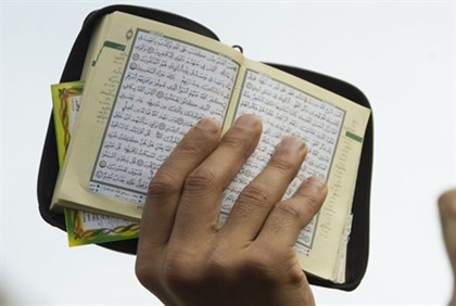 Muslim holds up copy of koran