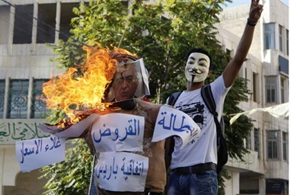 Protester gestures as he stands near a burning effigy of Fayyad