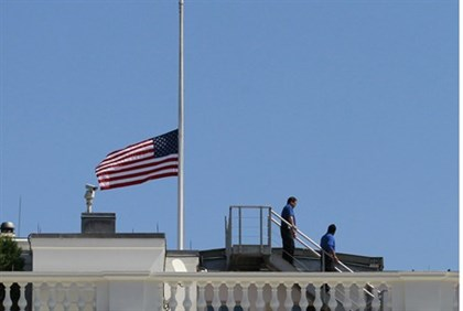 White House staff are pictured after they lowered the U.S. flag to half staff on the roof of the Whi