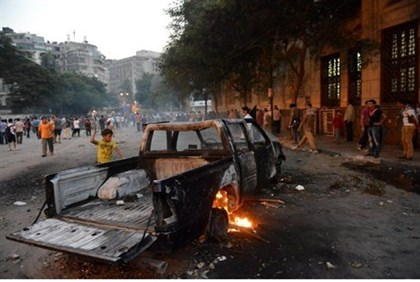 Burnt pick-up truck during clashes between protesters and riot police in Cairo