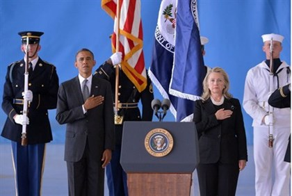 US President Barack Obama (L) and Secretary of State Hillary Clinton listen to the National Anthem