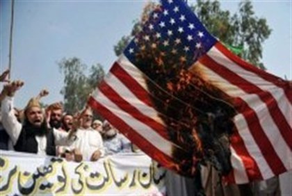 Pakistani Muslim protesters burn a US flag during a rally against an anti-Islam movie in Peshawar