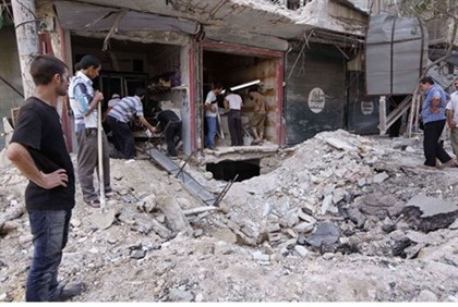 Civilians view debris from Syrian gov't air strike in Aleppo